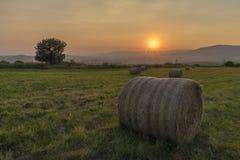 Palle del fieno con il tramonto sopra le montagne Immagini Stock