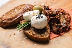 Palle del formaggio di Labne con pane nero, olive verdi ed i semi di senape fotografia stock libera da diritti