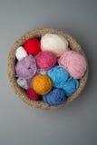 Palle della lana di colore in ciotola a foglie rampanti su Grey Background Fotografie Stock Libere da Diritti