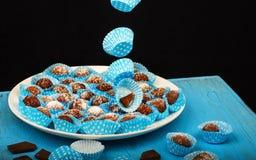 Palle di carta decorative blu volanti del cioccolato e del canestro sul piatto Fotografia Stock