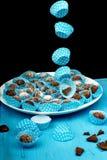 Palle di carta decorative blu volanti del cioccolato e del canestro sul piatto e sulla tavola blu Fotografie Stock Libere da Diritti