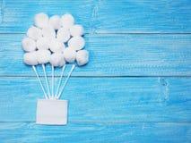 Palle di cotone assorbente e germogli bianchi del cotone su fondo blu di legno fotografia stock libera da diritti