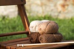 Palle di lana in tonalità dei toni naturali su una sedia Fotografia Stock Libera da Diritti