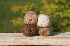 Palle di lana in tonalità dei toni naturali su vecchio legno Immagini Stock Libere da Diritti