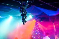 Palle di Natale che appendono nel club con le luci colorate luminose ed il fondo vago Immagini Stock Libere da Diritti