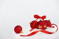 4 palle di natale con il nastro che cade neve Fotografie Stock Libere da Diritti