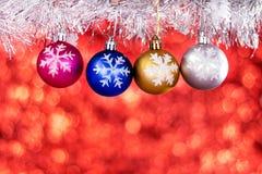 Palle di Natale con la decorazione di Natale sul bokeh di rosso della sfuocatura Immagine Stock