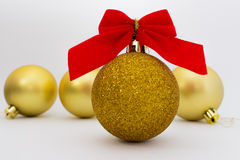 Palle di Natale dell'oro con il nastro rosso su fondo bianco Immagine Stock