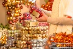 Palle di Natale di acquisto del compratore in scatole di plastica Fotografia Stock Libera da Diritti