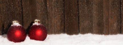 Palle di Natale nella neve davanti a fondo di legno Fotografia Stock Libera da Diritti