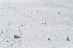 Palle di neve che rotolano giù un pendio nevoso sopra la montagna fotografia stock libera da diritti