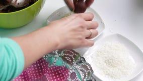 Palle di rotoli di una donna da una miscela per le caramelle in una polvere di sesamo video d archivio