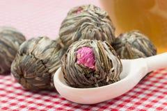 Palle di tè verde con i fiori, la tazza di tè ed il cucchiaio di legno Immagine Stock Libera da Diritti