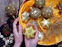 Palle dorate di Natale in scatola e stella d'oro in mani Decorazione di natale Fuoco selettivo Fotografia Stock Libera da Diritti