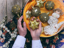 Palle dorate di Natale in scatola e stella d'oro in mani Decorazione di natale Fuoco selettivo Immagine Stock Libera da Diritti