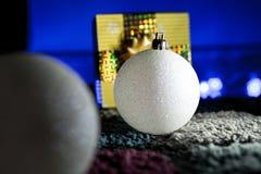 Palle frizzanti di natale bianco con il regalo nel fondo Fotografia Stock