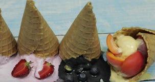 Palle fuse dolci del gelato in un cono della cialda Bacche differenti e frutti stock footage
