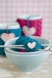 Palle luminose di filato in piatti blu e di cuore fatto di feltro Fotografia Stock