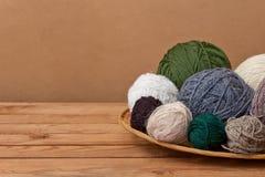 Palle multicolori del filato in un canestro della paglia su una tavola di legno Immagini Stock Libere da Diritti