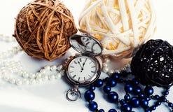3 palle, orologi e perle sui precedenti bianchi Fotografie Stock Libere da Diritti