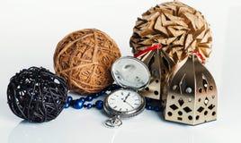 3 palle, orologi e perle sui precedenti bianchi Fotografia Stock