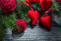 Palle rosse dei cuori dei rami di albero dell'abete sul bordo di legno fotografia stock libera da diritti