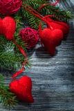 Palle rosse dei cuori dei rami di albero dell'abete sul bordo di legno d'annata immagine stock libera da diritti