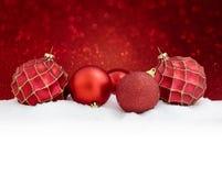 Palle rosse di natale su neve con il fondo di scintillio Carta di Buon Natale Fotografia Stock Libera da Diritti