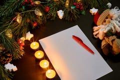 Palle rosse e taccuino di Natale che si trovano vicino al ramo attillato verde sulla vista superiore del fondo nero Spazio per te Fotografia Stock