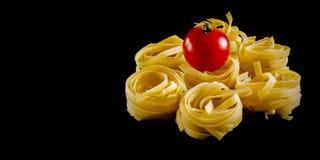 Palle rotonde di pasta cruda con il pomodoro su fondo nero Isolato fotografia stock