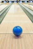 Palle sul vicolo di bowling contro dieci perni Fotografie Stock