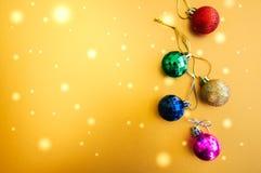 Palle variopinte di Natale su un fondo dorato Fuoco selettivo Fotografie Stock Libere da Diritti