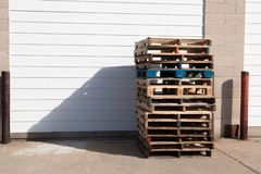 Pallet di spedizione di legno impilati contro la porta di costruzione del garage fotografia stock