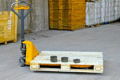 Pallet jack. Hand powered pallet jack in wooden warehouse Stock Photos
