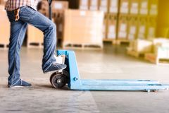 Pallet-Jack Man. A worker pallet-jack on the load area under blurred box stacking background Royalty Free Stock Image