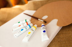 Pallet and oil paint tubes lying on white canvas Royalty Free Stock Image