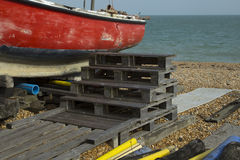 Pallet steps leading to a red fishing boat Stock Photography