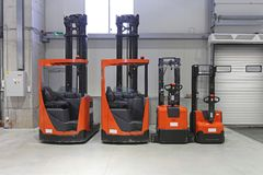 Pallet Trucks and Forklifts. In Distribution Warehouse Stock Photos
