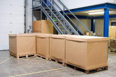 Pallets with cartons in warehouse. Pallets With brown carbord Cartons In big Warehouse Stock Photos