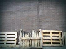 Pallets die op bakstenen muur leunen Stock Fotografie