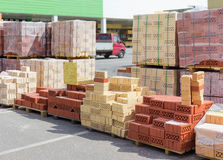 Pallets of perforated red and yellow bricks on warehouse Stock Photos
