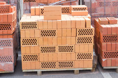Pallets of perforated yellow and red bricks on warehouse Royalty Free Stock Photos