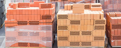 Pallets of perforated yellow and red bricks on warehouse Stock Image