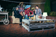 Pallets table with beverages and confetti in party. Pallets table with beverages and confetti on top in a outdoors party with people talking in the background Royalty Free Stock Photo