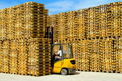 Pallets walls. Forklift operator inside row of wooden euro pallets Royalty Free Stock Photos