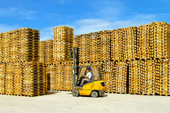 Pallets warehouse. Forklift operator inside row of wooden euro pallets Stock Photo