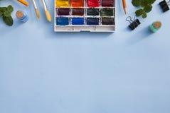 Pallette akwareli paintbrushes dla malować i farby niebieska tła kosmos kopii zdjęcia royalty free