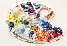 Pallette artístico con las pinturas de aceite en el papel en blanco Imagen de archivo