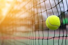 Pallina da tennis che colpisce alla rete sulla corte della sfuocatura fotografia stock