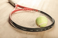 Pallina da tennis che si trova sulla racchetta su una superficie di legno Fotografia Stock Libera da Diritti